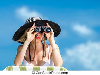 Beautiful young woman in bikini looking through binoculars...