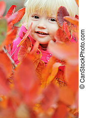 peekaboo - happy girl in fall bushes