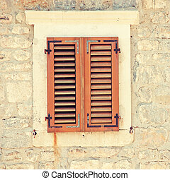 Vintage image with window and shutters in old rough stone...