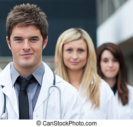 Handsome young doctor leading his team and looking at the...