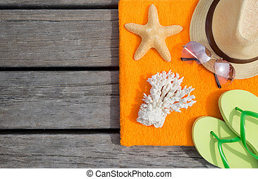 Beach slippers, towel and starfish on wood background....