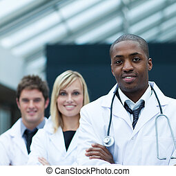 Portrait of a confident ethnic doctor leading his team