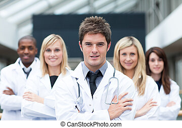 Handsome young doctor leading his team with folded arms