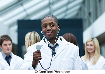 Ethnic doctor with his team in the background smiling at the...