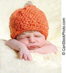 pumpkin - sleeping newborn wearing pumpkin hat