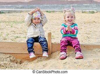 happy childhood - happy toddlers sitting in sand