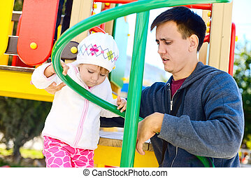 father and daughter on the playground