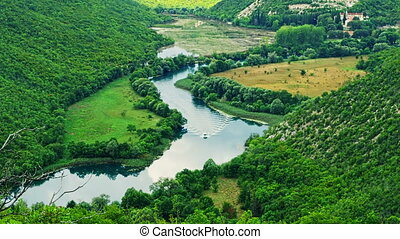 Krka river flow - Tourist boat floats Krka river in a...