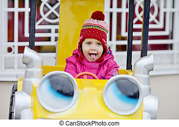 toddler girl in theme park showing tongue