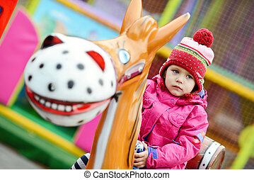 toddler girl  in theme park  on the horse