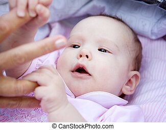 Cute baby girl holding parent hands - Close up portrait of a...