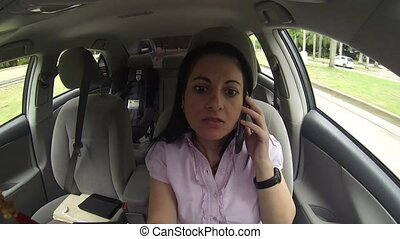 Woman talking on mobile phone in the car