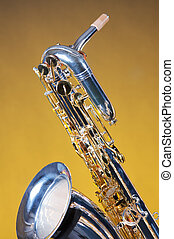 Saxophone Baritone Isolated on Yellow - A silver and gold...