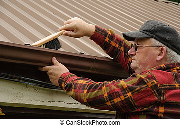senior male cleaning out gutter - senior male cleaning out...