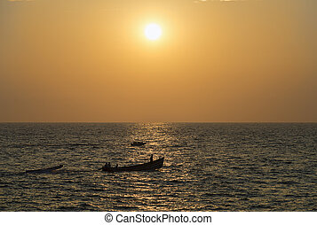 Boats in ocean at sunset