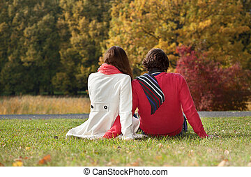 Couple sitting on the ground in the park - Young couple...