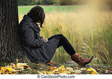 Autumn melancholy - Woman contemplating alone in the autumn...
