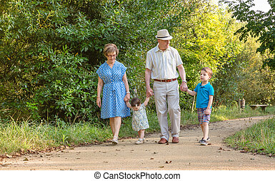 Grandparents and grandchildren walking outdoors - Front view...