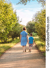 Grandmother and grandchild walking on a nature path - Back...