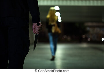 Man with knife following woman at night
