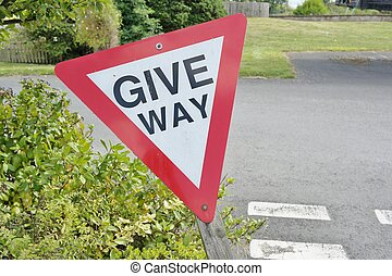 triangular give way sign against tarmac road and grass and...