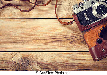 Old Camera - Old retro camera on wooden table background...