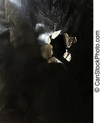Bullet hole in a piece of metal, side view...
