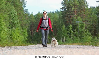 Young woman with dog walking.