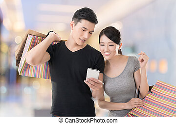 shopping and looking at cellphone - Young Asian couple...