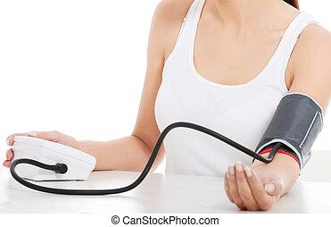 Woman measures her blood pressure