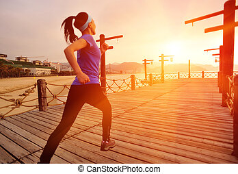 Runner running on seaside boardwalk - Runner athlete running...