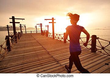 runner running on seaside boardwalk - Runner running on...