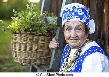 Old woman in Slav folk costume near a village house, a...