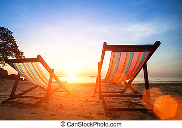 Loungers on the beach deserted oceanside at amazing sunrise