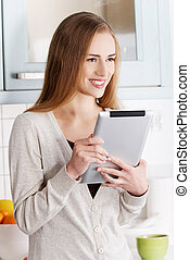 Young woman using a tablet computer at home