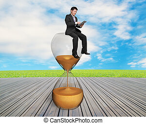 man using smart pad sitting on sandglass with nature sky and...