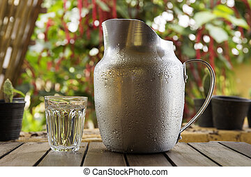 A Glass and Metal Jug of water on a wooden table