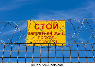 sign prohibiting passage on the fence with barbed wire