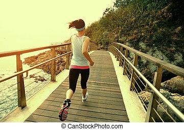 Runner running at wooden boardwalk - Runner athlete running...