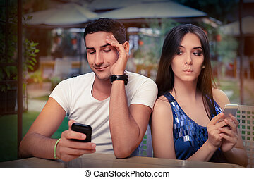 Secretive Couple with Smart Phones - Young adult couple has...