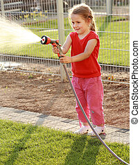 Watering - Little girl watering the grass in the garden