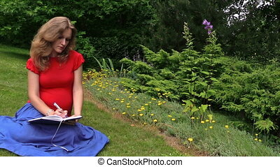 woman write diary park - beautiful young woman write diary...