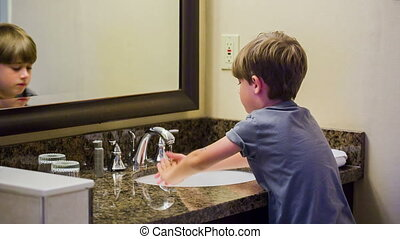 Child washing hands in the bathroom