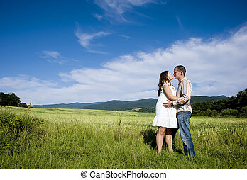 Pregnant couple kissing in nature - Happy young pregnant...