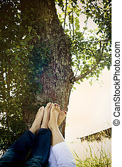 Close up of bare feet of young couple lying in park under...