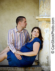 Happy pregnant couple is relaxing by the old house