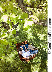 Pregnant couple in nature on sofa