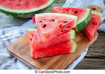 slices of fresh juicy organic watermelon on a wooden...