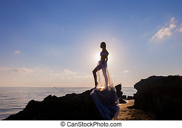 Woman enjoying freedom feeling happy at beach at sunset. -...