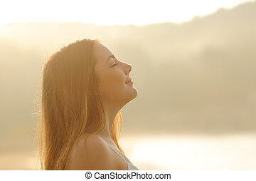 Woman breathing deep fresh air in the morning sunrise -...